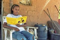 Latynoska nastoletnia dziewczyna czyta storybook Fotografia Stock