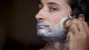 Latynoska pochodzenie etniczne mężczyzny pokrywa jego policzki golić piany lustra spojrzenie zdjęcie wideo