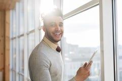 Latynoski Biznesowy mężczyzna Używa komórka telefonu Mądrze stojaka w frontowym Panoramicznym Nadokiennym Szczęśliwym Uśmiechnięt obraz royalty free