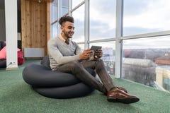 Latynoski Biznesowy mężczyzna Używa pastylka komputer Siedzi n Frontowego Panoramicznego Nadokiennego Szczęśliwego Uśmiechniętego obraz stock