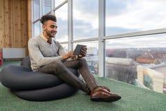 Latynoski Biznesowy mężczyzna Używa pastylka komputer Siedzi n Frontowego Panoramicznego Nadokiennego Szczęśliwego Uśmiechniętego zdjęcia stock