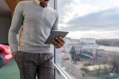 Latynoski Biznesowy mężczyzna Używa pastylka komputeru stojaka w frontowym Panoramicznym Nadokiennym biznesmenie W Coworking cent Obraz Stock