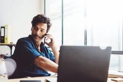Latynoski coworker pracuje na nowożytnym mobilnym komputerze podczas gdy siedzący przy drewnianym stołem przy pogodnym biurem Męż Fotografia Stock
