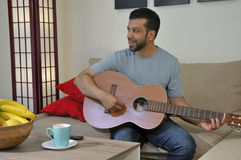 Latynoski facet Bawić się gitarę w domu Fotografia Royalty Free