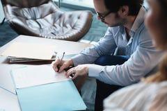 Latynoski kierownika podpisywania dokument Z sekretarką W Biznesowym biurze obraz royalty free