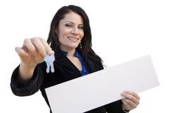 Latynoski kobiety mienia pustego miejsca znak i klucze Na bielu Obrazy Stock