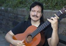 Latynoski mężczyzna bawić się gitarę akustyczną outdoors Obrazy Stock