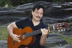 Latynoski mężczyzna obsiadanie w parkowej bawić się gitarze Zdjęcia Stock