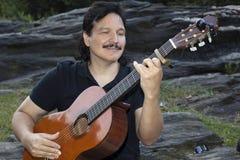 Latynoski mężczyzna obsiadanie w parkowej bawić się gitarze Obrazy Royalty Free