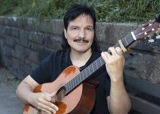 Latynoski mężczyzna obsiadanie z klasyczną gitarą Zdjęcie Royalty Free