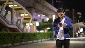 Latynoski mężczyzna używa telefon przy nocą podczas gdy badający miasto ulicy zdjęcie wideo