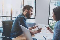 Latynoski młody biznesmen pracuje z partnerem biznesowym przy pogodnym biurem zamazujący tło horyzontalny Zdjęcia Royalty Free