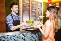 Latynoski pracownik daje sałatki klient zdjęcia stock