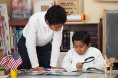 Latynoskie chłopiec w szkoły studiowania skałach Fotografia Royalty Free