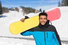 Latynoskiej mężczyzna chwyta Snowboard ośrodka narciarskiego zimy Śnieżny Halny Rozochocony Szczęśliwy Uśmiechnięty facet fotografia stock