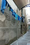 Lauandry som torkar i en pittoresk liten gata i en by i Calabria, Italien royaltyfri fotografi