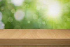 Laub bokeh Hintergrund mit leerem Holztisch. Lizenzfreie Stockbilder