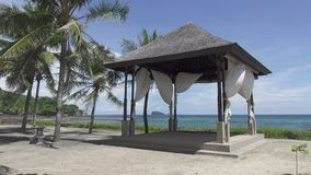 Laube unter Palmen auf der Bank des tropischen Strandes im Seebad stock video