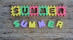 Laubsäge schriftliches Sommerwort auf hölzernem Hintergrund Stockbild