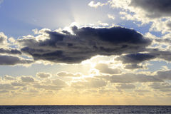Lauderdale By The Sea Morning Sun. Beautiful sun streaming golden yellow white sunlight from behind a large blue cloud over the Atlantic Ocean off the coast of Stock Photography