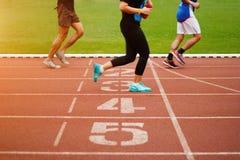 Laufbahnzahl und laufende Übung der Leichtathletikleute stockfotos