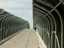 Laufen über eine Fußgängerbrücke Lizenzfreies Stockfoto