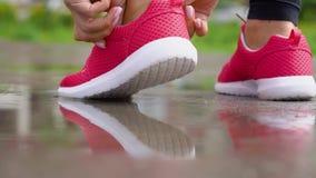 Laufen in regnerisches Wetter Frauenbindungen ihre Spitzee und Anfänge zu laufen R?ckseitige Ansicht Langsame Bewegung stock video footage