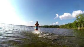 Laufen in Richtung zum See auf einem Badeanzug stock video footage