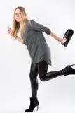 Laufende blonde Modefrau mit schwarzer Kupplung Stockbild