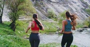 Laufende Damen mitten in erstaunlicher Landschaft an der Natur mit einem geeigneten Körper sie das Training zusammen tuend, haben