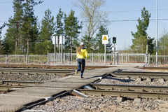 Laufende Eisenbahnen des nicht identifizierten Mädchens an einem Fußgängerübergang auf einem grünen Verkehrslichtsignal Lizenzfreies Stockfoto
