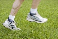 Laufende Füße im grünen Gras Stockfoto