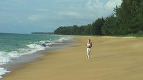 Laufende Frau, die auf Strand rüttelt stock video