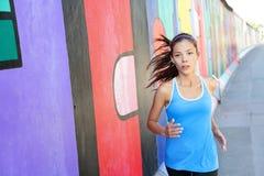 Laufende Frau, die durch Berlin Wall, Deutschland rüttelt Lizenzfreie Stockfotos
