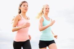 Laufende Frauen, die auf Strand rütteln Lizenzfreie Stockbilder