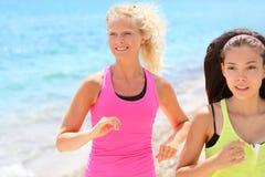 Laufende Frauen, die auf Strand rütteln Lizenzfreie Stockfotos