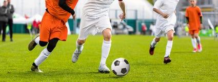 Laufende junge Fußball-Fußball-Spieler Fußballspieler, die Footb treten stockfotografie