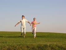 Laufende Paare auf Gras lizenzfreie stockfotos