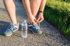 Laufende Schuhe Barfüßiglaufschuhe schließen oben Männlicher Athlet, der Spitzee für das Rütteln auf Straße bindet Läuferbindunge stockfoto