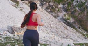 Laufende sportliche Dame durch die erstaunliche Gebirgsstraße beim Halten der Flasche des Wassers und der hörenden Musik unter Ve