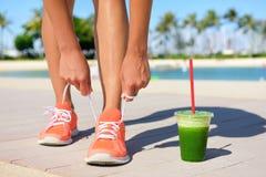 Laufender Frauenläufer mit grünem Gemüsesmoothie stockfotos