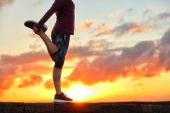 Laufender Läufer, der das Bein sich vorbereitet für Lauf ausdehnt lizenzfreies stockbild