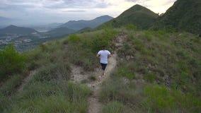 Laufender Mann, der auf Gebirgsschneise bei Sonnenuntergang trainiert Manneslauf, arbeiten aus