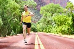 Laufender Mann, der Herzfrequenzmonitor smartwatch schaut Stockfotos