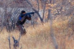 Laufender Mann mit einem Gewehr Stockbilder