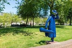 Laufender Mann mit Violinenkasten statuet Stockbild