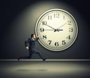 Laufender Mann und große weiße Uhr Stockfotos
