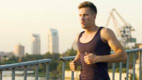 Laufender Marathon des hübschen Kerls, der seine Gesundheit und Form, Zeitlupe beibehält stock video