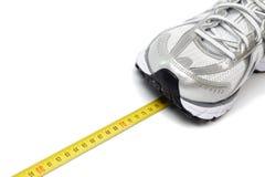 Laufender Schuh und Zentimeter stockbild