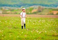 Laufendes blühendes Feld des aufgeregten netten Jungen, Frühlingslandschaft stockbild